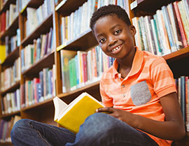 Smiling young man sitting cross-legged on the floor with a book open, leaning against library stacks