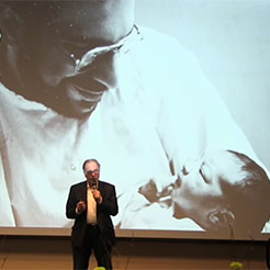 Robert Naseef presenting in front of a picture of him as a new father with his newborn son Tariq