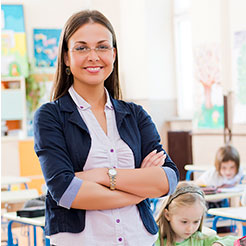 Smiling young teacher stands with arms crossed in front of rows of her students